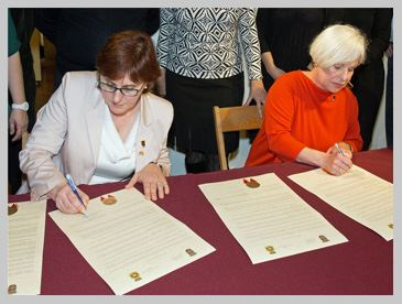 The mayor of St. Augustine and the mayor of Aviles Spain signing compassionate city proclamations