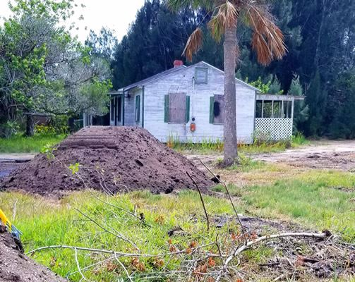 Photo of cottage on Coquina property with dirt pile