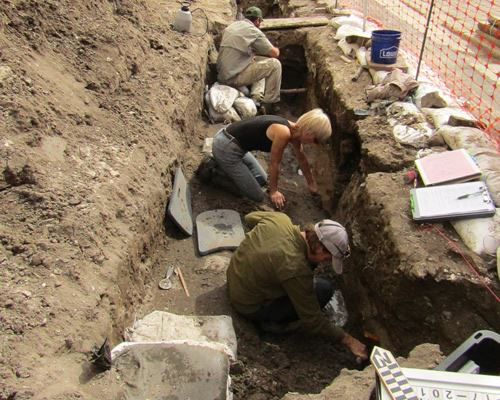 Archaeology team of three people digging in a trench on Charlotte Street at the site of Los Remedios