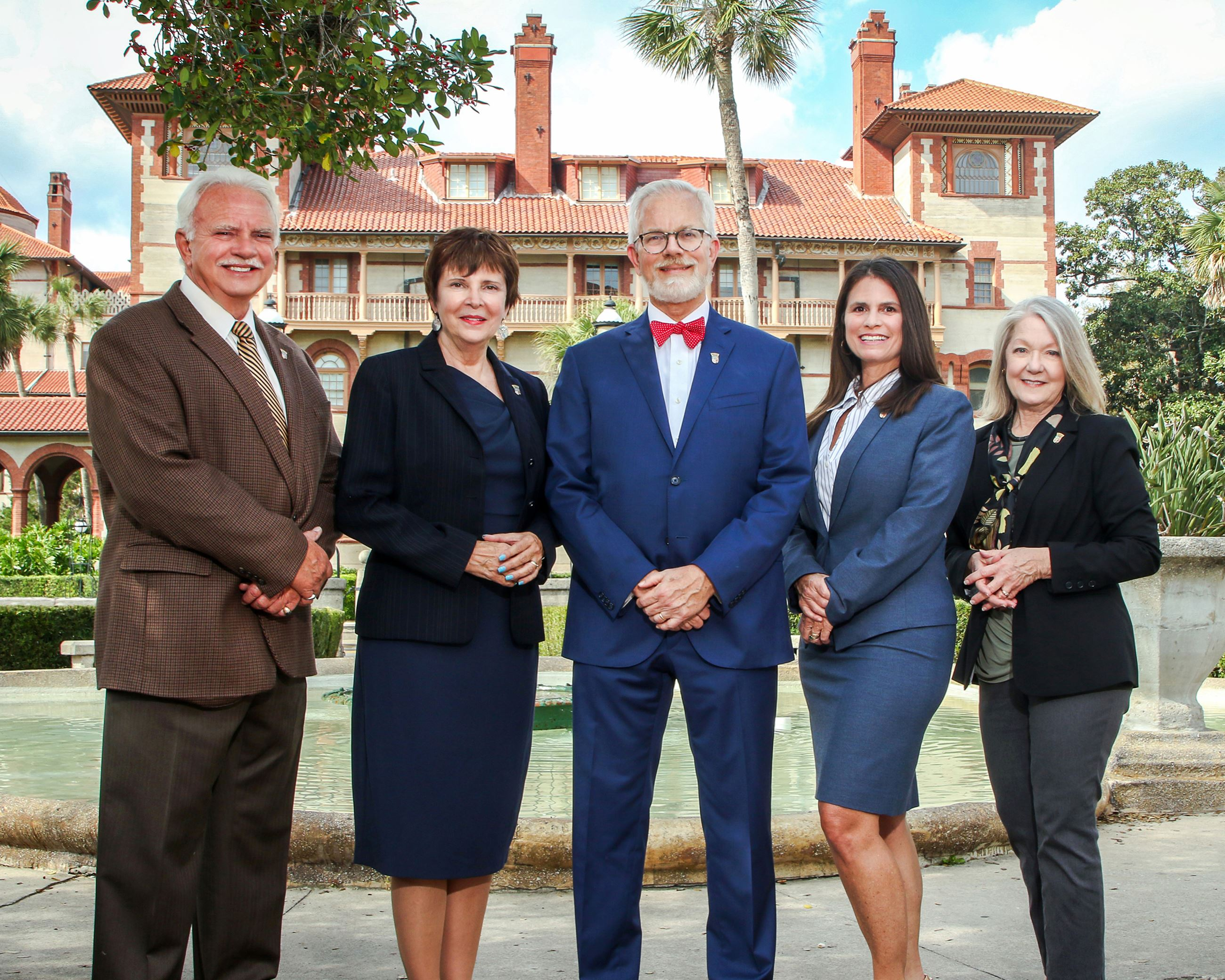 5 people standing in front of a fountain with Flagler College building behind
