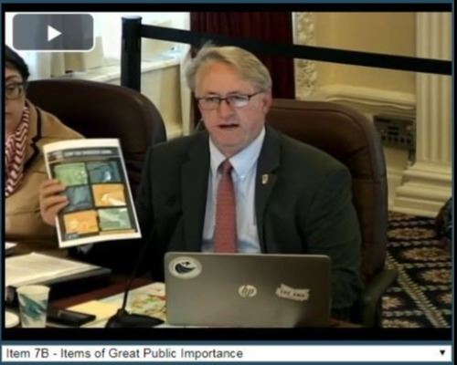 City Manager is sitting at a desk behind a laptop computer holding a piece of paper with a Centers f