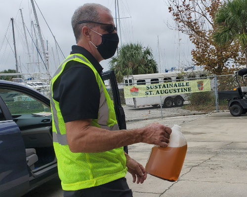 City worker carrying used oil for recycling