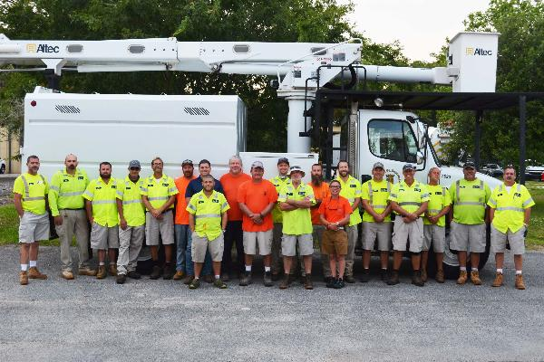 Streets and Grounds Crew standing in front of a city construction vehicle